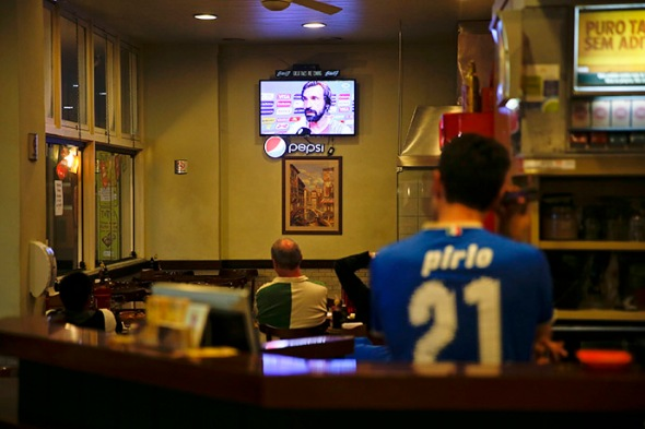 A Brazilian man of Italian origin wears a jersey of Andrea Pirlo as Andrea Pirlo appears on TV screen in a restaurant in Porto Alegre following Italy's win over England in a 2014 World Cup Group D match