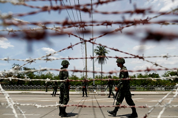 "Thai soldiers man a checkpoint near pro-government ""red shirt"" supporters encampment in suburbs of Bangkok"